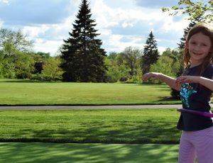 girl with hula hoop outdoors