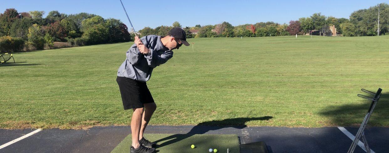 man swinging golf club at driving range